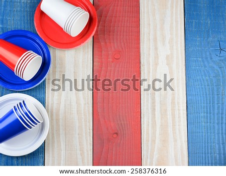 High angle shot of a red, white and blue picnic table with matching plates and cups. The cups and plates are set ot one side leaving copy space. - stock photo