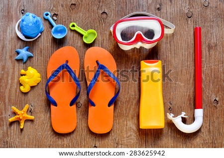 high-angle shot of a rustic wooden table full of summer stuff, such as a starfish, a diving mask and a snorkel, a bottle of sunblock, a pair of flip-flops and some beach toys - stock photo