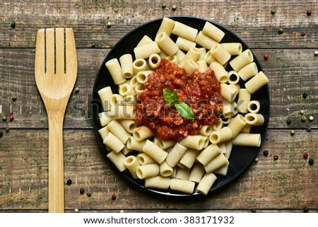 high angle shot of a wooden fork and a black plate with penne rigate with bolognese sauce on a rustic wooden table - stock photo