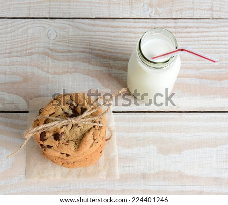High angle shot of an after school snack of chocolate chip cookies and an old fashioned bottle of milk. The cookies are tied with twine and  on a rustic wood kitchen table, with copy space. - stock photo