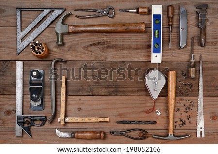 High angle shot of an assortment of contractors well used tools. Horizontal format on a rustic wood background, with a bland space in the middle of the tool arrangement. - stock photo