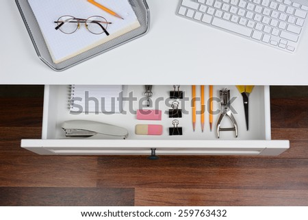 High angle shot of an open desk drawer showing the items inside. The top of the desk has a computer keyboard and wire in-box with paper and pencil. The drawer has pencils, erasers, stapler and more. - stock photo