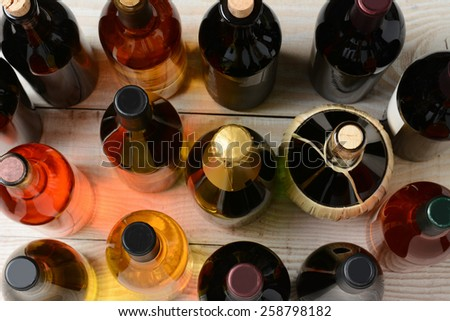 High angle shot of assorted wine and champagne bottles on a rustic wood table. Horizontal format. - stock photo