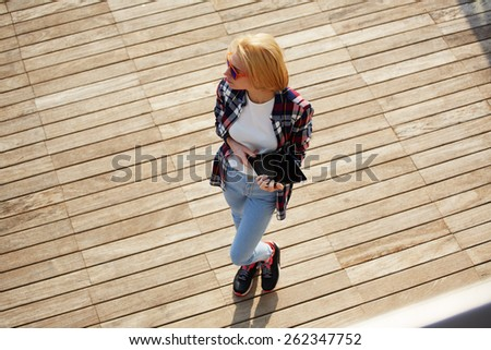 High angle shot of beautiful young woman holding her digital tablet standing on a wooden floor, caucasian college student holding tablet while standing at campus looking away - stock photo
