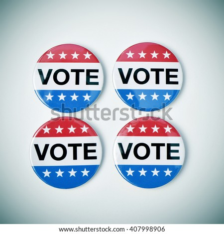 high-angle shot of four vote badges for the United States election on a white surface, with a slight vignette added