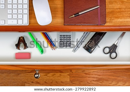 High angle shot of open desk drawer with basic work items inside. Cherry wood desktop has computer keyboard, mouse and executive notepad with pen. Wooden oak floors underneath desk.  - stock photo