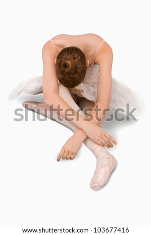 High angle shot of sitting ballerina against a white background