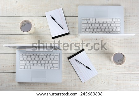 High angle shot of two computer work stations back-to-back with almost identical layouts. Horizontal format on a whitewashed wood table. - stock photo