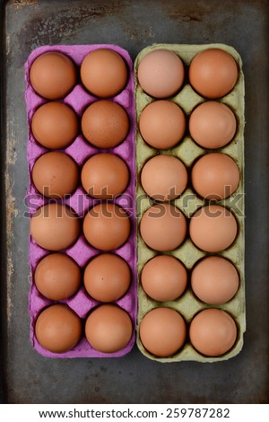 High angle shot of two one dozen cartons of organic brown eggs on a well used cooking surface.. Vertical format. - stock photo