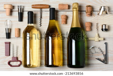 High angle shot of Wine and Champagne bottles surrounded by accessories such as corkscrews, stoppers, pourers and corks. Horizontal format on a rustic white wood table. - stock photo