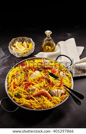 High Angle Still Life of Appetizing Seafood Paella Made with Yellow Noodles and Variety of Shellfish Served in Metal Pan with Handles on Table with Fork and Accompanied by Lemon Wedges and Olive Oil