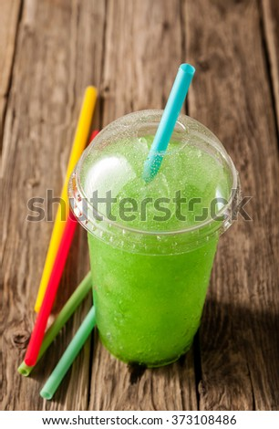 High Angle Still Life of Plastic Cup Filled with Refreshing Frozen Green Slush Drink and Served on Rustic Wooden Table with Colorful Drinking Straws - stock photo