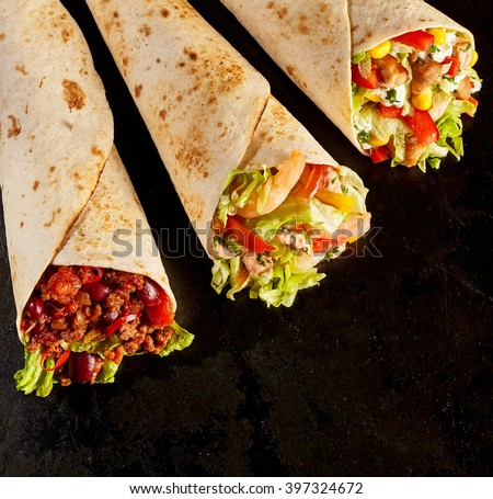High Angle Still Life of Trio of Tex Mex Fajita Wraps on Black Background - Variety of Grilled Flour Tortilla Wraps Stuffed with Different Fillings Such as Chicken, Shrimp and Chili - with Copy Space - stock photo