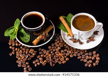 High Angle Still Life of Two Cups of Black Coffee Garnished with Fresh Mint, Cinnamon Sticks and Star Anise on Black Surface with Roasted Coffee Beans - stock photo