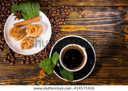 High Angle Still Life View of Cup and Saucer of Black Coffee Garnished with Fresh Mint Sprig and Served with Plate of Dainty Gourmet Pastries on Wood Table Scattered with Roasted Coffee Beans - stock photo