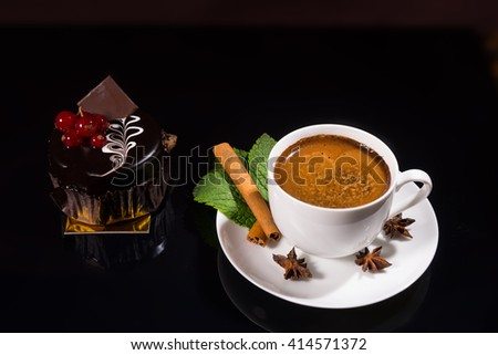 High Angle Still Life View of Frothy Gourmet Espresso Coffee Garnished with Fresh Mint Leaves, Cinnamon Stick and Star Anise Served with Dark Chocolate Individual Cake Garnished with Red Berries - stock photo