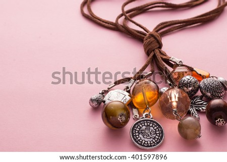 High Angle Still Life View of Handmade Artisan Jewellery on Pink Background - Stylish and Funky Necklace Made with Brown Leather and Adorned with Silver Charms, Wood Beads and Stones - stock photo