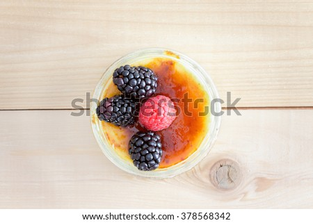 High Angle Still Life View of Single Serving Indulgent Creme Brule Custard Dessert Topped with Raspberry and Blackberry Fruit Garnish Served on Wooden Table Surface - stock photo