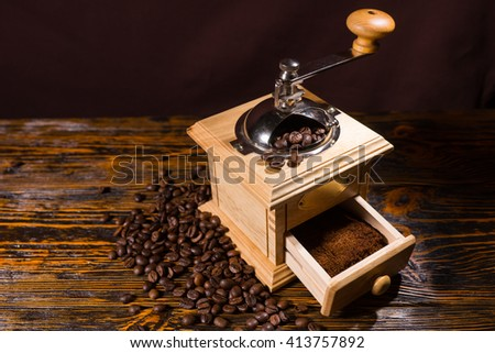 High Angle Still Life View of Traditional Wooden Hand Grinder with Fresh Ground Coffee on Rustic Wooden Table with Roasted Coffee Beans and Copy Space