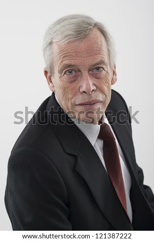 High angle studio portrait of a serious handsome grey haired senior man in a suit and tie looking up at the camera - stock photo
