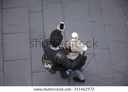 High angle view of a couple walking down the street using a Smart Phone. Young man and woman walking together. - stock photo