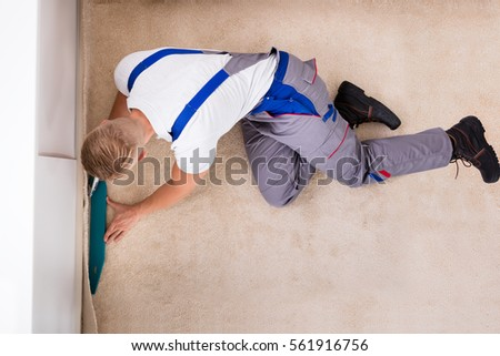 high angle view of a craftsman installing carpet on floor