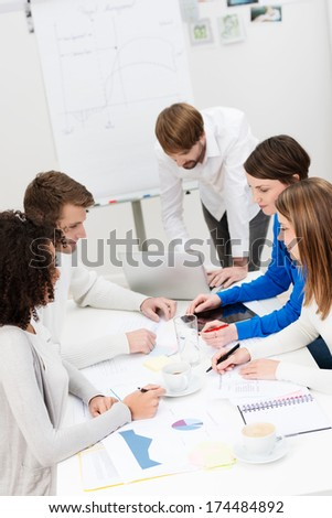 High angle view of a dedicated young business team in a meeting sitting around a table comparing notes and information - stock photo