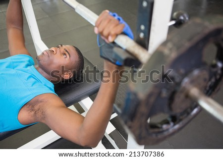 High angle view of a determined young muscular man lifting barbell in gym - stock photo