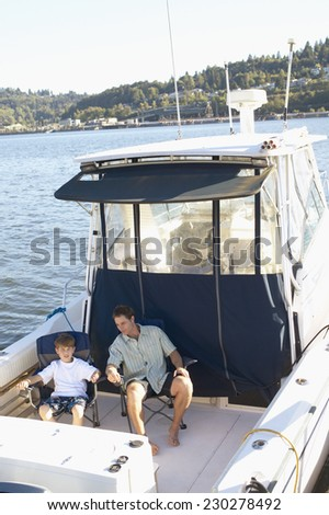 High angle view of a father and his son sitting on folding chairs on a boat - stock photo