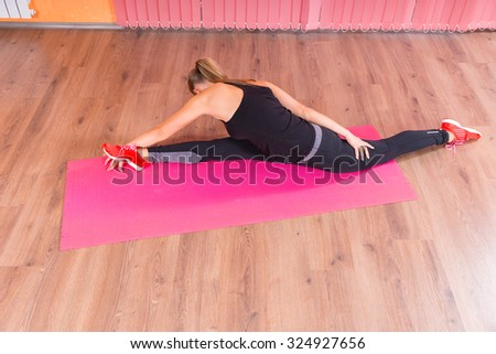 High Angle View of a Flexible Young Woman Splitting her Legs While Stretching her Upper Body on Top of a Fitness Mat. - stock photo