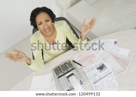 High angle view of a frustrated African American woman with documents and receipt expense at home - stock photo