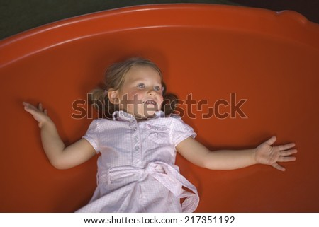 High angle view of a girl lying on a trampoline - stock photo