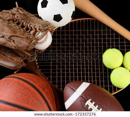 High angle view of a group of assorted sporting gear. Items include, Baseball, basketball, soccer ball, football, tennis racket, glove and bat over a black background. - stock photo