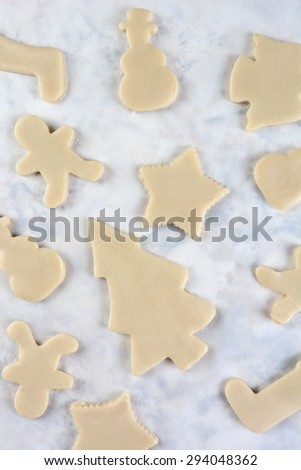 High angle view of a group of raw dough Christmas cookie shapes on parchment paper. Vertical format.