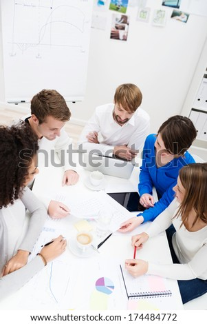 High angle view of a group of young business partners in a meeting seated around a table discussing a new project - stock photo