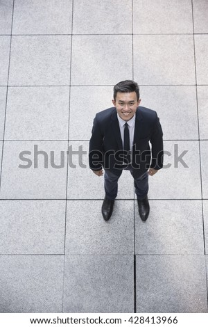 High angle view of a happy Asian businessman looking at the camera. - stock photo