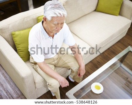 high angle view of a lonely senior asian man sitting on couch.