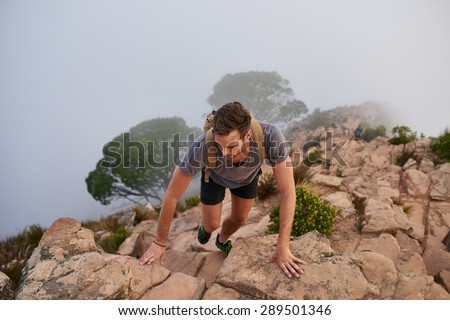 High angle view of a male hiker climbing up rocks on a mountain with mist below - stock photo