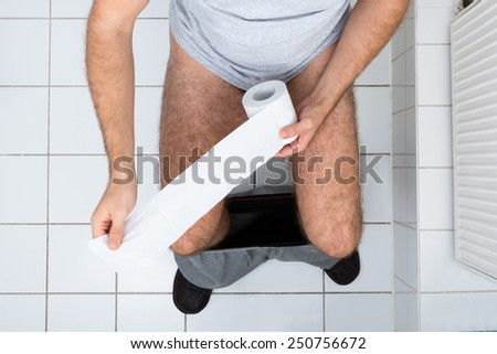 High Angle View Of A Man In Toilet Holding Tissue Paper - stock photo