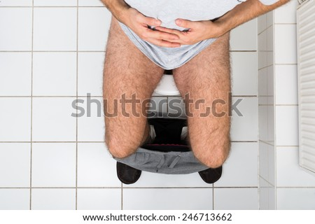 High Angle View Of A Man In Toilet Suffering From Stomachache - stock photo