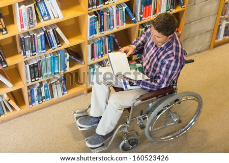 High angle view of a man in wheelchair reading a book in the library - stock photo