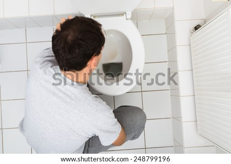 High Angle View Of A Man Vomiting In Commode - stock photo