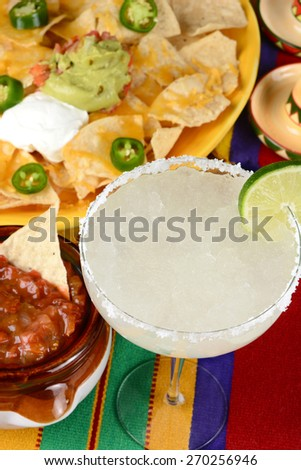 High angle view of a margarita cocktail surrounded by nachos, chips, salsa on a bright Mexican, table cloth. Vertical format. Perfect for Cinco de Mayo projects. - stock photo