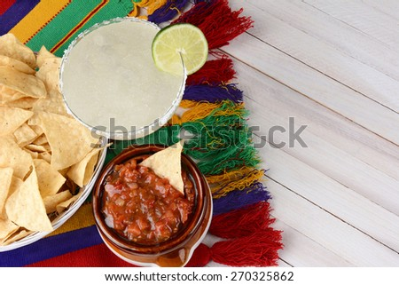 High angle view of a margarita cocktail with chips and salsa on a white rustic wood table. Horizontal format with copy space. Cinco de Mayo theme. - stock photo