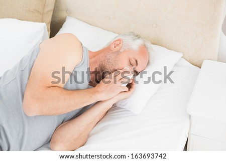 High angle view of a mature man suffering from cold as he lie in bed at home