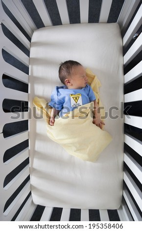 High angle view of a newborn baby sleeping in a crib - stock photo