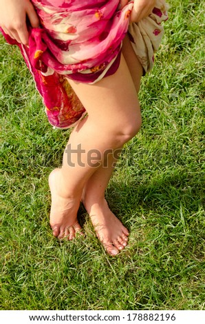 High angle view of a pair of sexy shapely barefoot female legs posing on green grass as she holds aside the fabric of her long skirt - stock photo