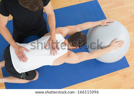 High angle view of a physical therapist assisting young man with yoga ball in the gym at hospital - stock photo