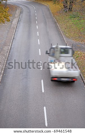 High angle view of a pick up truck on small asphalt road in the fall - stock photo