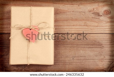 High angle view of a plain brown paper wrapped Valentines Day present with a red heart gift tag. Horizontal format on a rustic wood surface with copy space with instagram effect. - stock photo